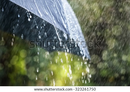 Rain drops falling from a black umbrella concept for bad weather, winter or protection - stock photo