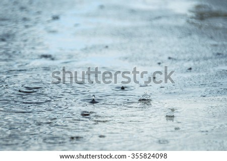 Rain drops in a puddle - stock photo