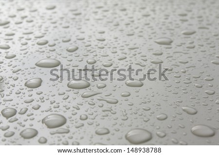 Rain drops on a body of white car.