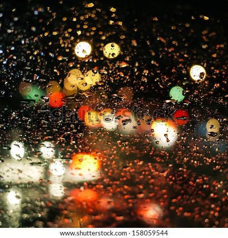 rain drops on car glass in rainy night - stock photo