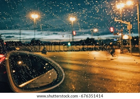 Rain drops on car window with road light bokeh, City life in night in rainy season abstract background,water drop on the glass, night storm raining car driving concept.