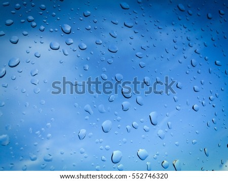 Rain drops on glass with Clear Blue Sky or Water drops of rain on Clear blue glass background