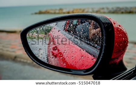 Rain drops on side-view mirror for car red.