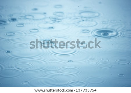 Rain drops on the blue water - stock photo