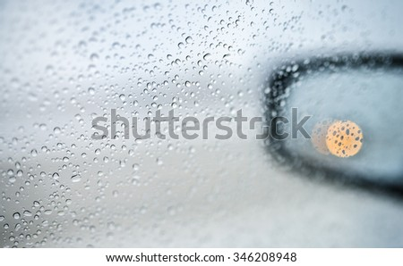 Rain drops on the side-view mirror of a car - stock photo