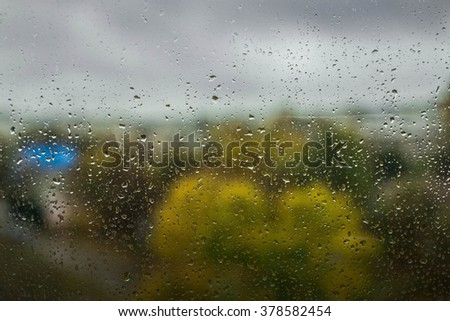 Rain drops on the window in the big city. trees on the background - stock photo