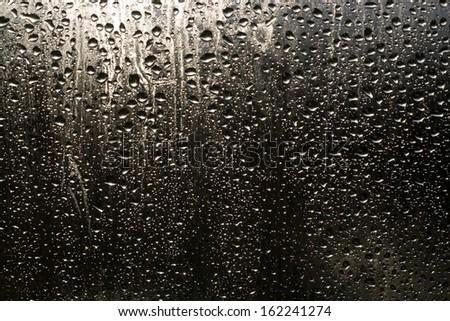 Rain drops on the window on the dark background - stock photo