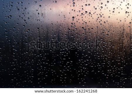 Rain drops on the window on the sunsret (dark-blue pink background) - stock photo