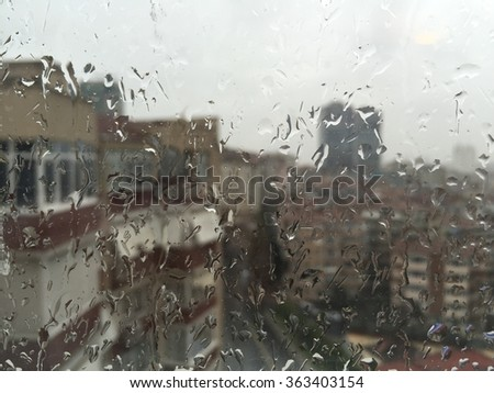 rain drops on window against buildings in a rainy day - stock photo