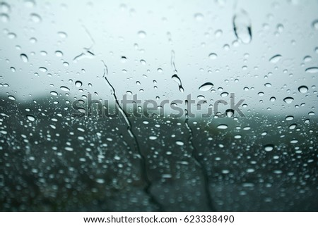 Rain drops on window glasses surface with cloudy background .