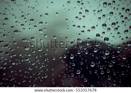 Rain drops on window. Green tone background.