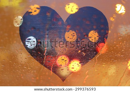 Rain drops on window with light bokeh on heart frame abstract background.
