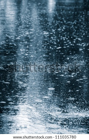 Rain drops rippling in a puddle - stock photo