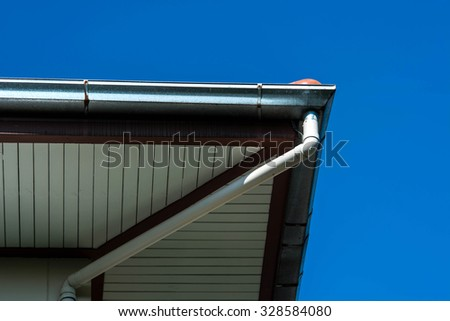 rain gutter on a roof against blue sky  - stock photo