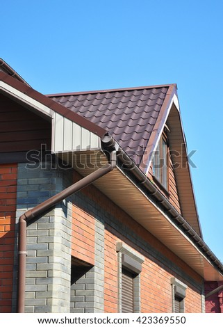 Rain gutter pipes against attic roofing.