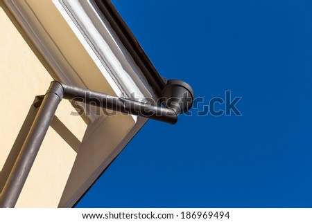 Rain gutters on old home. There is a blue sky in the background.