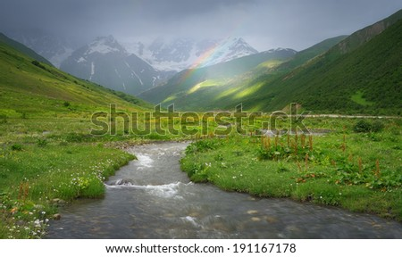 Rain in the mountains. Rainbow over the river. Mountain landscape on a rainy summer day. Caucasus, Georgia, Svaneti. View at the foot of the mountain Shkhara - stock photo