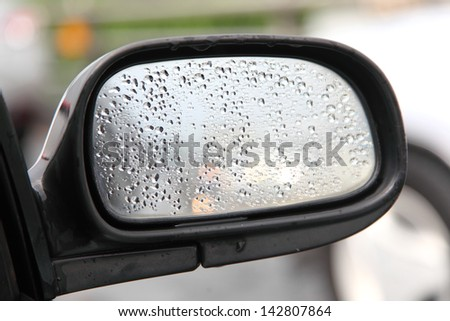 Rain on a car mirror - stock photo