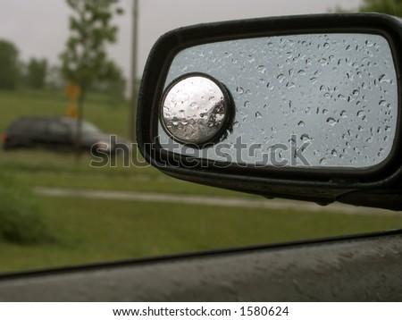 Rain on a car mirror. - stock photo