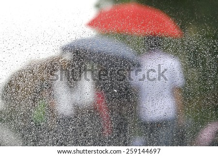 Rain on a window looking out to people in a street scene
