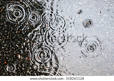 Rain on asphalt or tarmac road creating ripples, high contrast during autumn. - stock photo