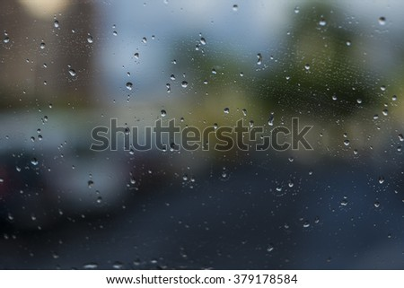 Rain on the glass in the car, de focus outside with lights