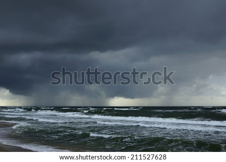 rain over Baltic sea - storm waves and overcast thunderstorm sky over water - stock photo