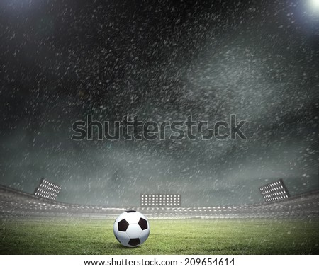 Rain pouring on stadium and soccer ball on grass - stock photo