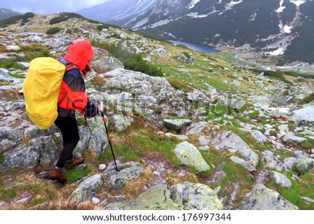 Rain pouring on the mountain and woman hiker - stock photo