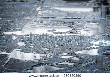 rain puddles on a pavement in the city - stock photo
