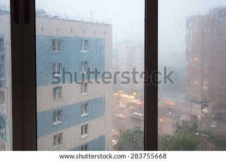 rain running down window panes at home in spring twilight - stock photo