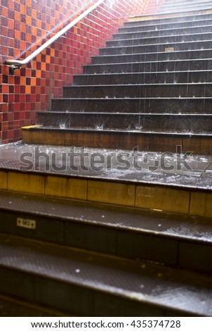 Rain splashes on the stairs in metro leading out of concrete pedestrian subway. Focus on rain.