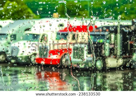 Rain streaming down a window with 18 wheeler trucks in the background.