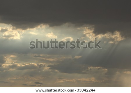Rain streams coming from glowing clouds - stock photo