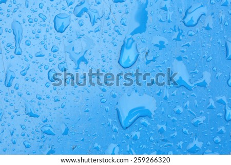 Rain water drops on blue background - stock photo