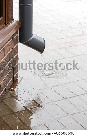rain water flow from drainpipe on paved sidewalk during rain - stock photo