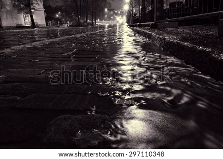 Rain water flowing down a street in down town Helsinki during a nightly autumn storm and creating miniature surge on a cobble street at Unioninkatu in Kaisaniemi district.   - stock photo