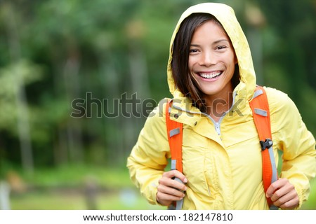 Rain woman hiking happy in forest. Female hiker portrait standing with backpack joyful on rainy day wearing yellow raincoat outside in nature forest by. Multi-ethnic Asian girl. - stock photo