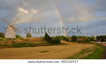 Rainbow above a typical grey Swedish windmill and fields with an orange VW T3 in the background (Sweden)