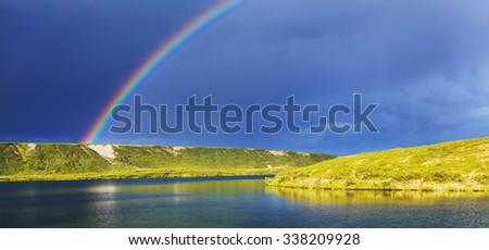Rainbow above mountains, Alaska - stock photo