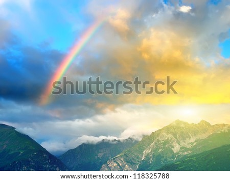 Rainbow and sunshine after rain in mountain valley. - stock photo