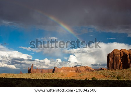 Rainbow appears after storm in Monument Valley desert USA - stock photo