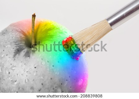 Rainbow apple close-up with water drops being painted on white background