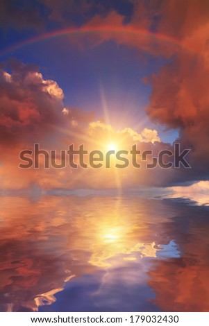 Rainbow at sunset reflected in the calm water - stock photo
