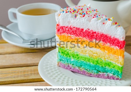 Rainbow cake with white tea cup on the wood table - stock photo