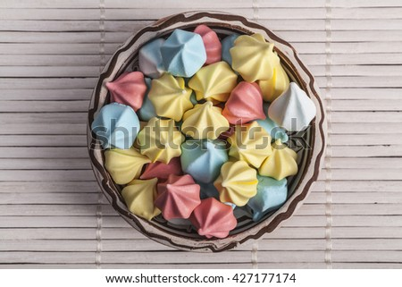 Rainbow circle sweets on plate on white wood - stock photo