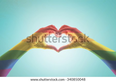 Rainbow color flag pattern on woman human hands forming in heart shape on blue vintage tone background: Symbolic equal rights in love and marriage social equality of LGBT community/ people concept    - stock photo