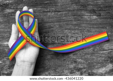 Rainbow color ribbon awareness on human hand on BNW background + clipping path:  Symbolic color logo icon for equal rights in love and marriage social equality of LGBT community/ people concept     - stock photo