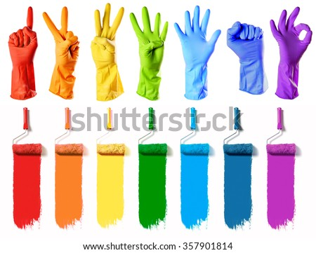 rainbow color rubber gloves on white with roller brushes with seven colors paint - stock photo
