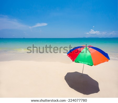 Rainbow color umbrella on empty ocean beach with waves - stock photo